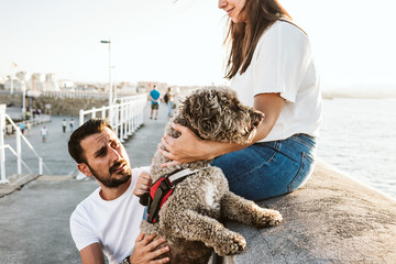 .Young and beautiful couple in love enjoying an afternoon outdoors near the port of Gijón, in Asturias (Spain). A fun and playful couple with their sweet Spanish Water Dog. Lifestyle. Love.