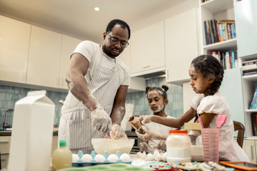 Two helpful funny daughters feeling involved in cooking with father
