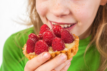Little girl eating cakes with fruits
