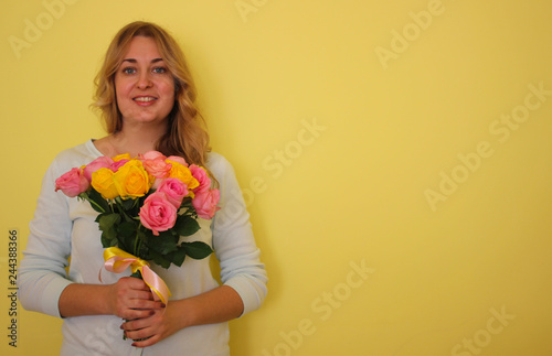 Beautiful blond girl in the blue dress holding bouquet of yellow and pink  roses on a f77925ab6