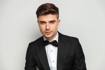 portrait of attractive man wearing black tuxedo and bowtie