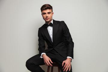 elegant man wearing black tuxedo sits on wooden stool