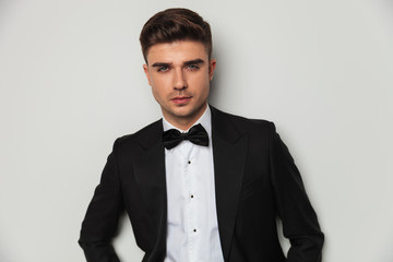 portrait of attractie groom wearing black tuxedo and bowtie standing