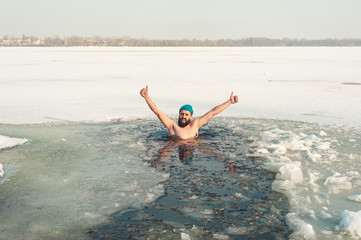 bearded man in hat in ice hole swimming