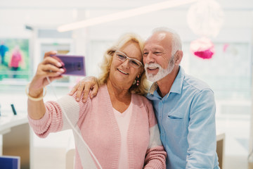 Grandparents taking selfie with smart phone they trying out while standing in tech store.