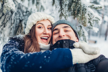Couple in love taking selfie and hugging in winter forest. Young happy people having fun. Valentine's day