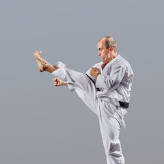 Adult man trains a direct kick in a jump on a gray background