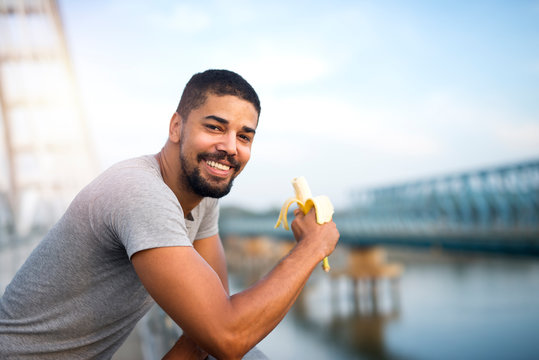 Young fit sporty person eating banana and smiling. Active lifestyle and healthy eating.
