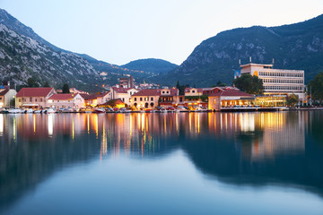 Lights of the evening city at sunset in the mountains. Reflection of houses in the water. Cozy evening in Montenegro.