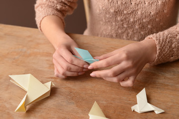 Young woman with origami bird at table, closeup