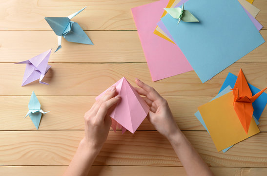 Young woman making origami on wooden table