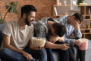 Friends watching comedy on TV and eating popcorn at home