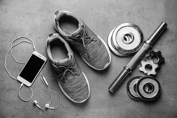 Shoes, sport equipment and mobile phone on grey background