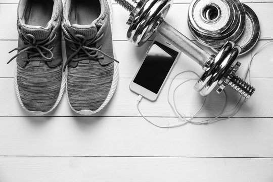 Shoes, sport equipment and mobile phone on white wooden background