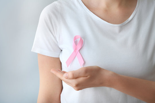 Woman with pink ribbon on light background, closeup. Breast cancer awareness concept