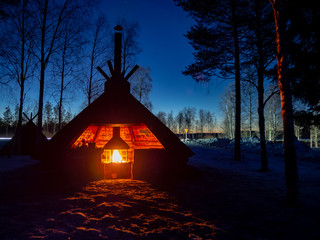 Lapland shelter with fireplace in winter night