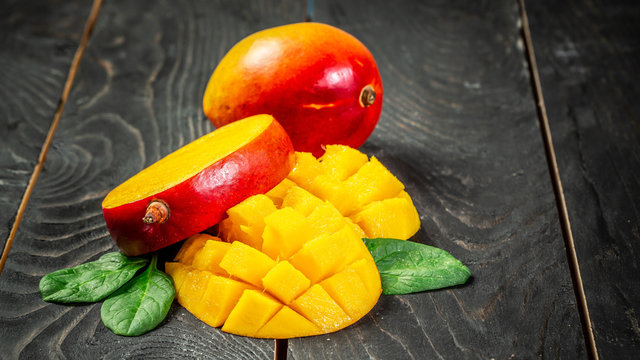 Fresh and beautiful mango fruit with sliced diced mango chunks on a dark wooden background, copy space text, blank for text, top view