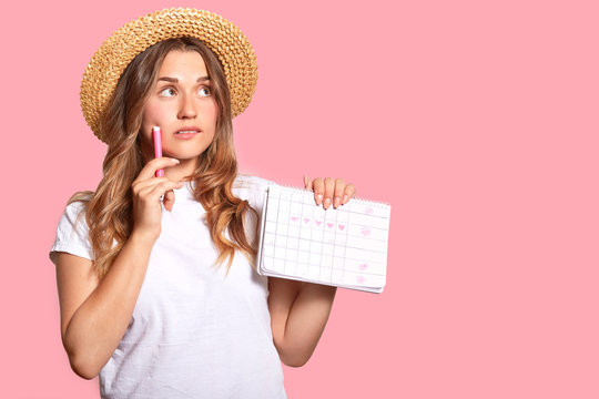 Horizontal shot of pleasant looking woman with thoughtful expression, wears headgear and casual t shirt, holds calendar with marked days, marker, poses over pink studio wall with empty space