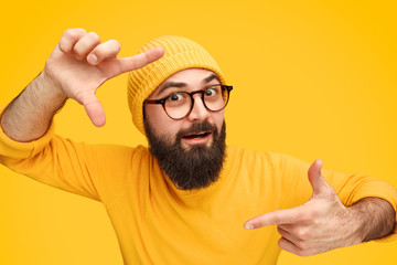 Bearded man holding hands in shape of camera focus