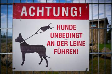 """Schild mit der Aufschrift """"Achtung, Hunde unbedingt an der Leine führen""""."""