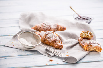 Fresh buttery croissants sprinkled with sugar powder on kitchen table.