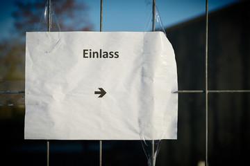 """Blatt Papier mit der Aufschrift """"Einlass"""" als Hinweis auf den Eingang zu einer Veranstaltung"""