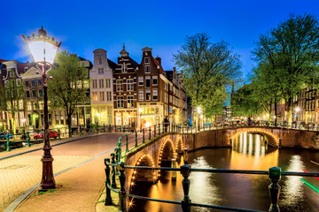 Amsterdam canal with typical dutch houses and bridge during twilight blue hour in Holland, Netherlands.