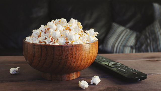 Wooden bowl of white salty popcorn and remote control on a wooden table in front of a couch. Front view, blurry background