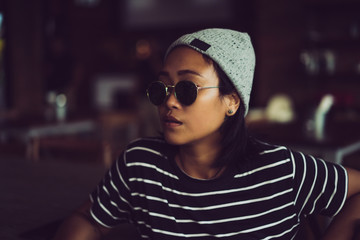 Indonesian girl hipster in a gray hat and sunglasses. Beautiful stylish Asian woman in tattoos.