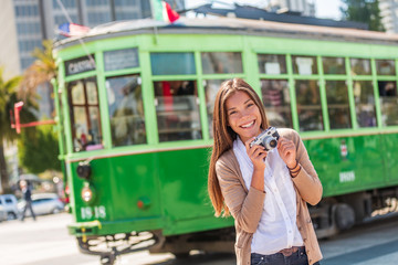 San Francisco cable car tramway woman tourist taking pictures of popular attraction vintage tram by the harbor. Asian girl photographer traveling in California, USA travel.