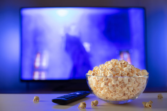 A glass bowl of popcorn and remote control in the background the TV works. Evening cozy watching a movie or TV series at home