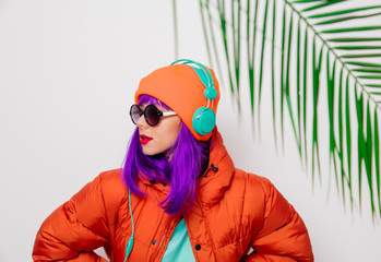 Portrait of a beautiful girl with purple hair in orange hat and jacket and with headphones on white background, palm branch. Trendy style