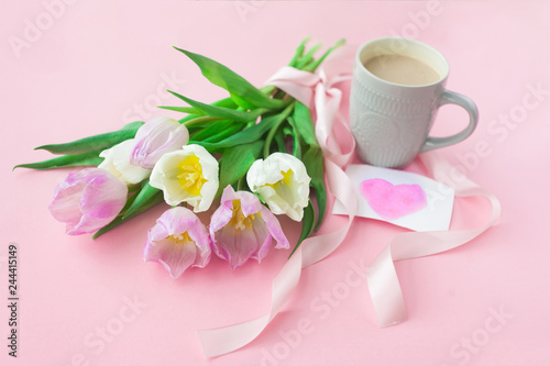Bouquet of tulips and a coffee cup on a pink pastel background. Wonderful spring breakfast on Mother's Day or Women. Flat lay. View top. Selective focus.