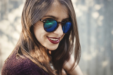 Stylish hipster girl smiling in sunny street on background of wooden wall. Boho girl in cool outfit and sunglasses posing in sunlight and shadow. Space for text. Summer vacation and travel