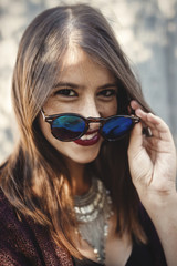 Stylish hipster girl smiling in sunny street on background of wooden wall. Portrait of boho girl in cool outfit and sunglasses posing in sunlight and shadow.  Summer vacation and travel
