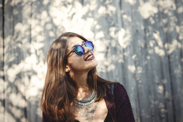 Portrait of happy boho girl in cool outfit and sunglasses smiling in sunlight. Stylish hipster girl posing in sunny street on background of wooden wall. Space for text. Summer vacation and travel