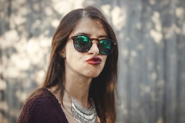 Portrait of happy boho girl in sunglasses having fun and smiling in sunny street. Stylish hipster carefree girl posing on background of wooden wall. Space for text. Summer vacation