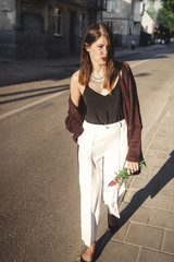 Stylish bohemian girl with modern jewelry walking in sunny street. Happy hipster carefree girl in boho look with flowers relaxing in evening summer city. Space for text. Summer vacation
