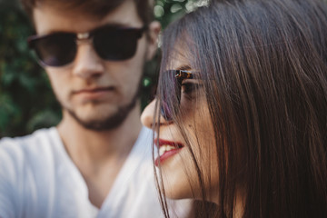 Stylish hipster couple in sunglasses posing and making cool selfie. Happy family couple in love making self portrait and embracing in evening summer city.