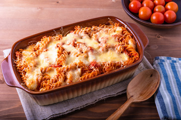 Baked fusilli pasta with mozzarella and tomato in a pan for baking on a wooden rustic background, top view.
