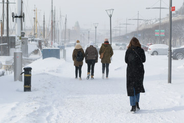 pedestrians on cold day with lots of snow in stockholm