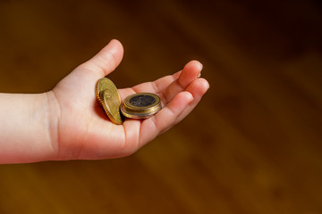 Child holding euro coin in his hand. Pocket money stock image. Poor low income group. Dark background. - Image. Close up.