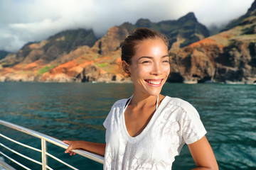 Wall Mural - Cruise ship boat tourist on Na Pali Coast of Kauai, Hawaii. Sunset cruise ride leisure activity happy Asian tourist in NaPali. Smiling Asian woman on deck having summer holiday.