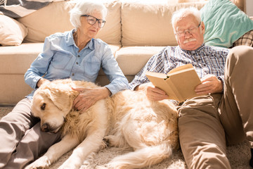 Portrait of happy senior couple cuddling with pet dog and reading books  sitting on floor at home  in sunlight