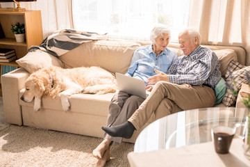 High angle portrait of modern senior couple using digital tablet sitting on couch at home in sunlight copy space