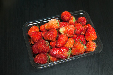 Close-up of fresh organic sweet strawberries in clear transparent  plastic container from marker or supermarket shop. Top view on black wooden background.