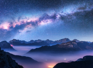 Milky Way above mountains in fog at night in autumn. Landscape with alpine mountain valley, low clouds, purple starry sky with milky way, city illumination. Aerial. Passo Giau, Dolomites, Italy. Space Wall mural