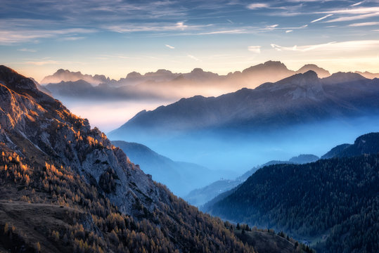 Mountains in fog at beautiful sunset in autumn in Dolomites, Italy. Landscape with alpine mountain valley, low clouds, trees on hills, village in fog, blue sky with clouds. Aerial view. Passo Giau