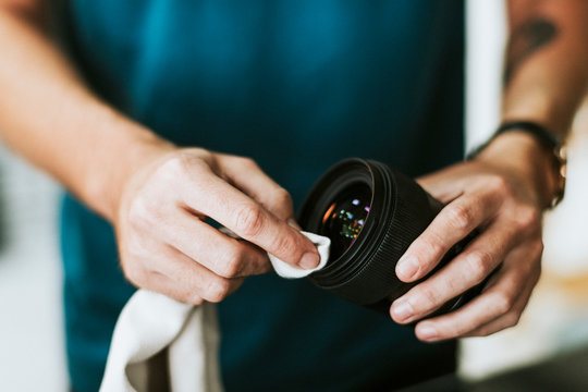 Photographer assistant cleaning a lens