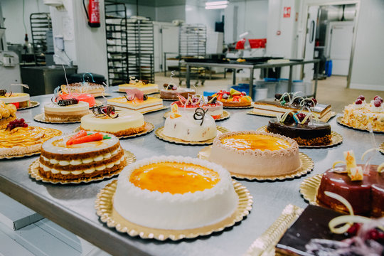 many cakes prepared on the metal table of a food factory